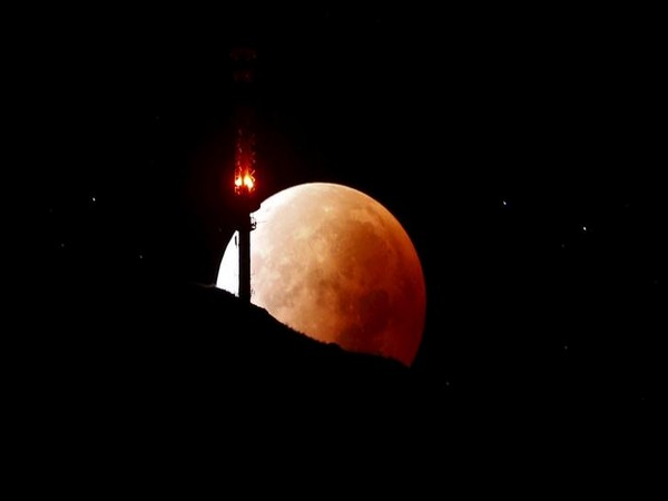 The moon, appearing in a dim red colour, is covered by the Earth's shadow during a total lunar eclipse over the peak of mount Rigi