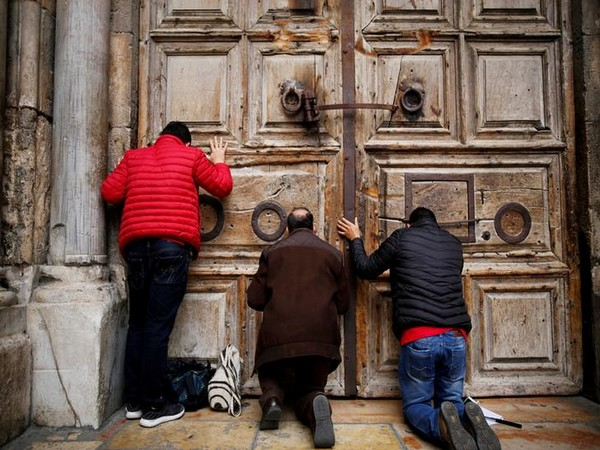 Worshippers kneel and pray in front of the closed doors of the Church of the Holy Sepulchre in Jerusalem's Old City