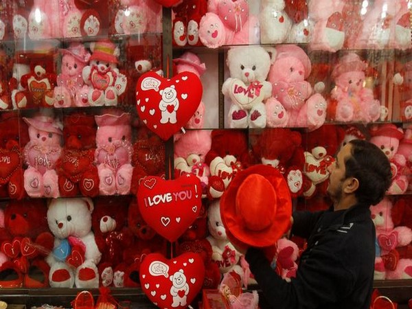 A shopkeeper hangs newly arrived stock at his shop ahead of Valentine's day in Peshawar