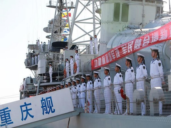 Chinese People's Liberation Army (PLA) navy soldiers stand on a decommissioned destroyer in an aircraft carrier theme park during a celebration event on China's Navy Day at Binhai New Area, Tianjin